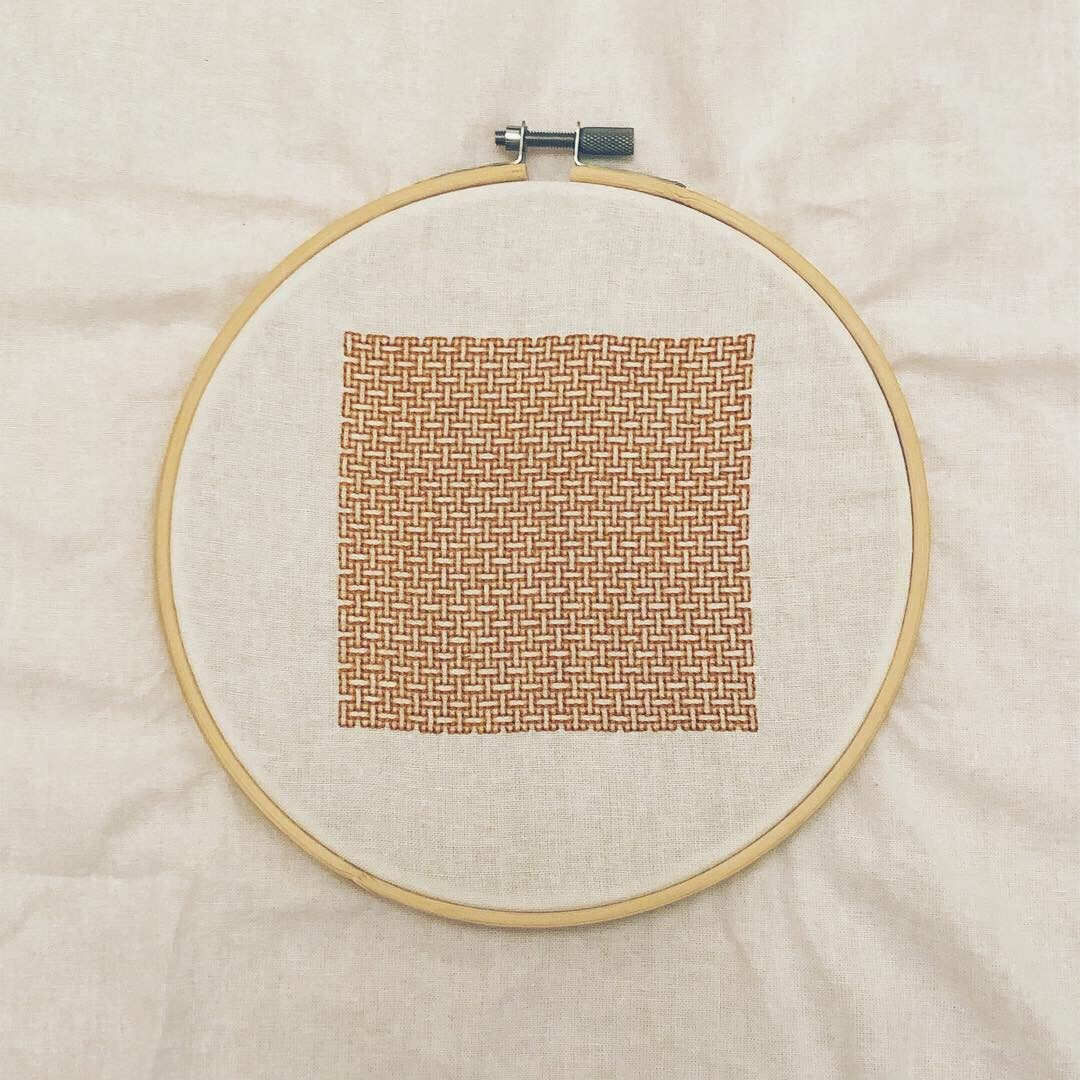 A square of amber embroidery in a weave pattern, on white fabric encircled by an embroidery hoop