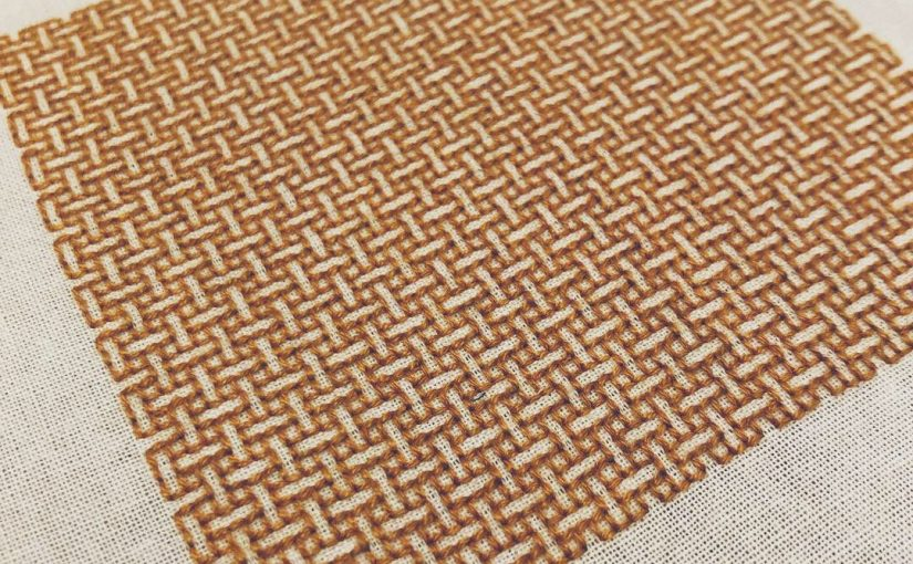 A close-up of the square of amber embroidery in a weave pattern, on white fabric